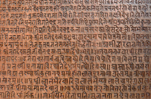 background with ancient sanskrit text etched into a stone tablet in a public square